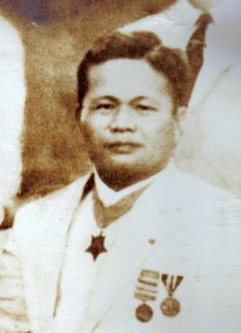 Middle aged Filipino American male wearing a white suite with a neck order medal, and two other medals on the lapel.