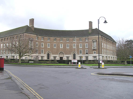 Red brick building with a curved façade seen across roads.