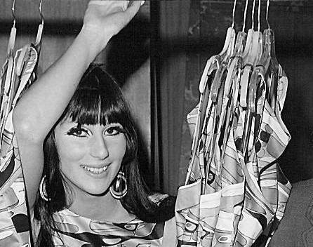 A black and white photograph of a young, dark-haired woman. She's raising her right arm, looking to the right and smiling. She is behind a curtain.