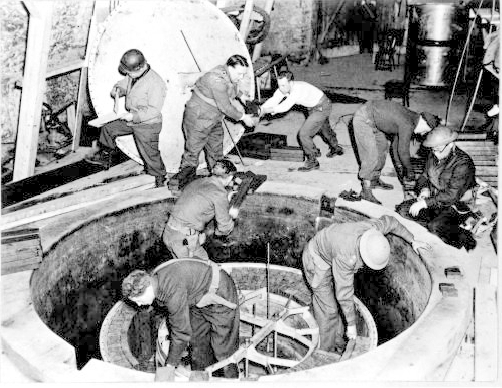 Soldiers and workmen, some wearing steel helmet, clamber over what looks like a giant manhole.