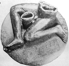 Black-and-white photograph of a statue consisting of an inscribed, round pedestal on top of which sits a seated nude male figure of which only the legs and lower torso are preserved.