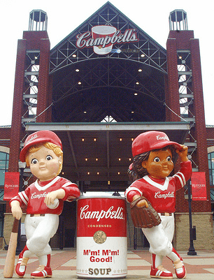 Outside of the stadium with two campbell's mascotts leaning on a campbell's soup can.