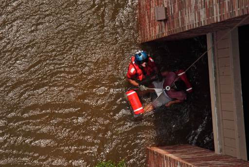 United States Coast Guard Scott D. Rady pulls a pregnant woman from her flooded New Orleans home