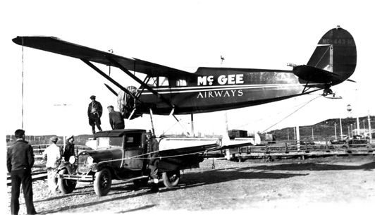 Black-and-white photo showing the left side of a seaplane being carried sideways on a truck.