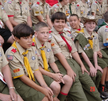 American Boy Scouts sitting around a campfire ring at a week long summer camp