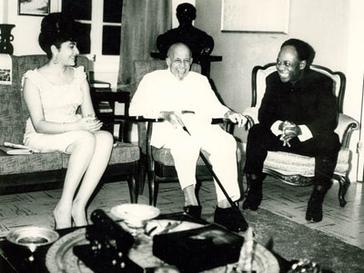 An elderly, smiling Du Bois sits in a chair, flanked by a man and woman also seated and smiling.