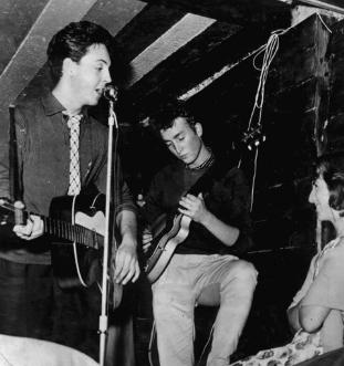 A youthful McCartney and Lennon perform in a low-ceilinged room with an audience member a few feet away.