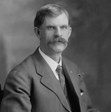 A man with dark hair and a prominent mustache wearing a black jacket, patterned tie, and white shirt