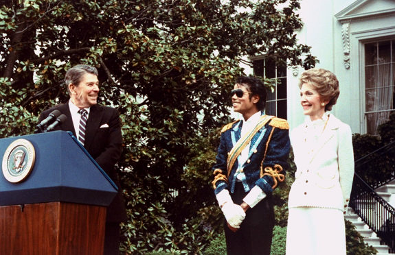 President Reagan wearing a suit and tie stands at a podium and turns to smile at Mrs Reagan, who is wearing a white outfit, and Jackson, who is wearing a white shirt with a blue jacket and a yellow strap across his chest.