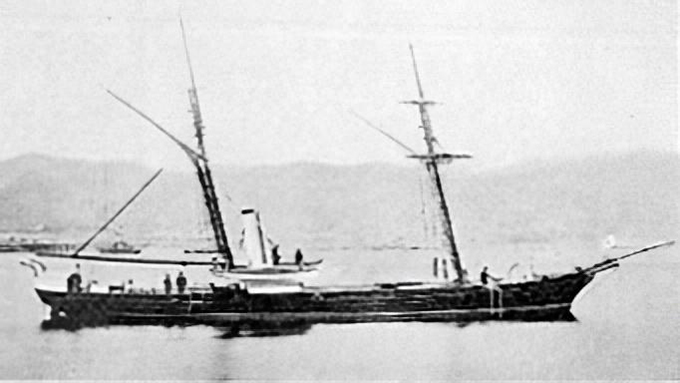 Small warship on flat sea, with smokestacks bent backwards.
