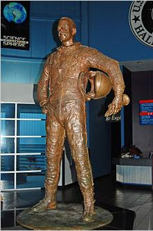 A bronze statue of Shepard weaing his Mercury space suit and carrying his space helmet under his arm.
