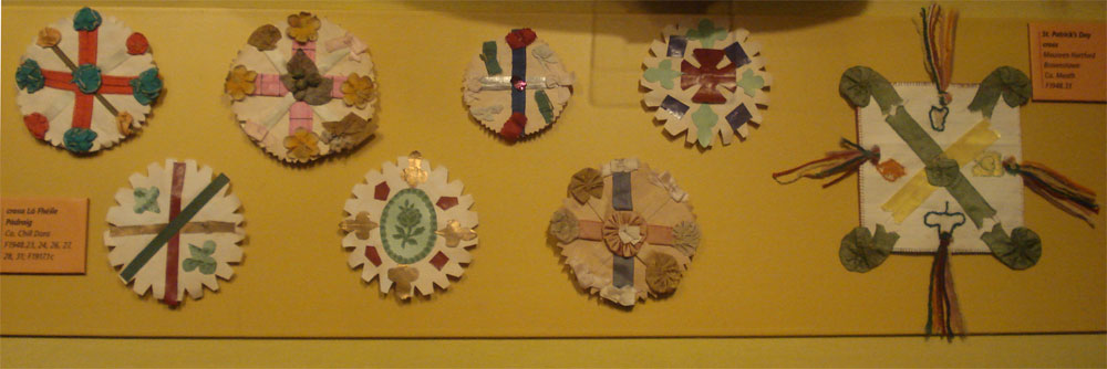 Photograph of eight home-made badges composed of variously coloured crosses and saltires.