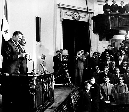Two men on a stage, with a flag hung behind them. One is reading from a paper, while the other is looking at the audience. Cameras are shooting the event, while most of the audience is looking at the stage.