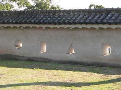 Photo of defensive loopholes in one of the castle walls. Two of the loopholes are rectangle-shaped, one is triangle-shaped, and one is circle-shaped.