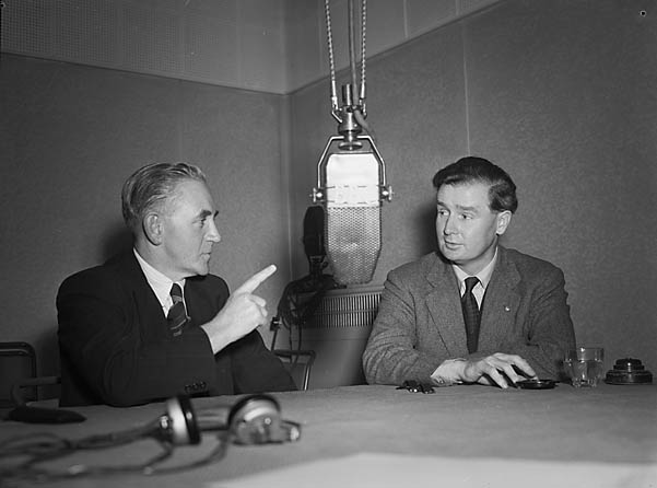 Iorwerth Thomas and Gwynfor Evans sitting at a table in front of a BBC microphone, debating.