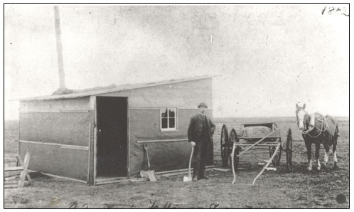 Unidentified man with horse and cart beside the first house built in Regina.