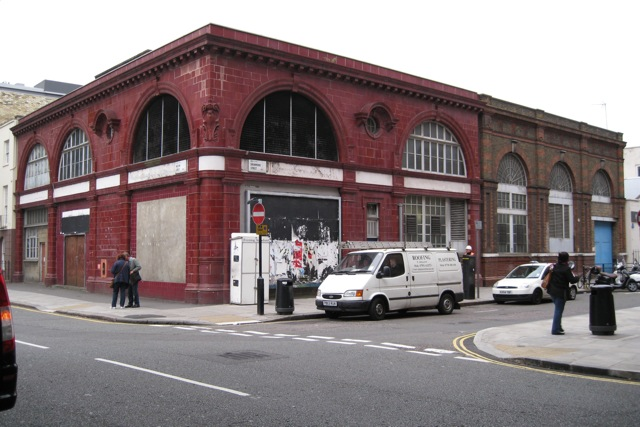 A red tiled building sited on a corner of a road junction. Five large, semi-circular windows fill much of the upper storey with the two on the corner removed and replaced with ventilation grilles.