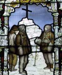 Three figures are depicted in coloured glass, standing by a cairn of snow topped by a large cross. The scene is framed by a decorative arch.