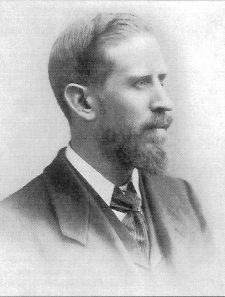 A black-and-white portrait photograph of a bearded man in a dark three-piece suit.