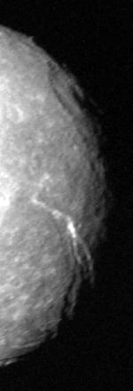 The right half of a round spherical body that is illuminated. The terminator runs along the right edge. A large crater with a central pit can be seen at the terminator in the upper half of the image. A large canyon runs from the darkness at the lower-right side to visible center of the body.
