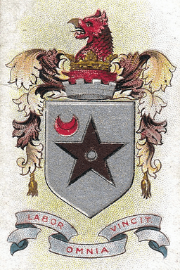 "A silver shield with a black five-pointed star with a red crescent in the top left hand corner. Above the shield are the battlements of a tower surmounted by a red griffin's head. Below the shield is the motto ""LABOR OMNIA VINCIT"", which means ""Persistent Works Triumphs""."