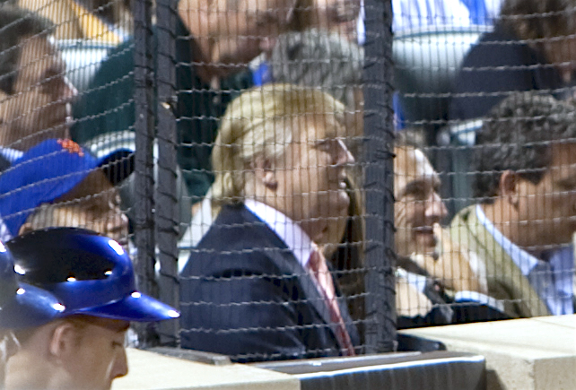 Trump at a baseball game in 2009. He is wearing a baseball cap and sitting amid a large crowd, behind a protective net.