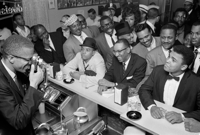 Malcolm X is holding a camera and taking a picture of Ali, who is sitting at a luncheonette counter