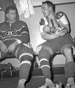 Richard, in full uniform except for his skates, sits on a locker room bench and stares at teammate Toe Blake beside him