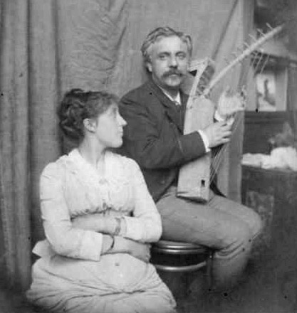 youngish couple in informal pose; the man is holding a small harp, the woman is looking at him