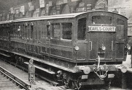 A three-quarter black-and-white photograph of a train standing at a station, showing the end carriage with windows at the end.