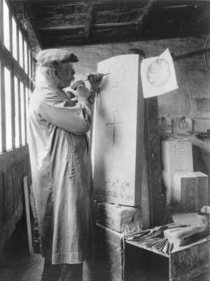 a man carving the a maple leaf onto a gravestone, in a workshop, with a hammer and chisel.