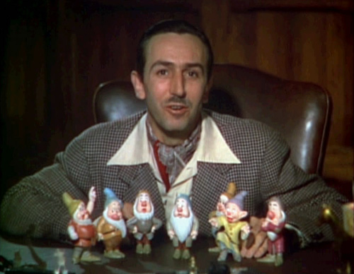 Walt Disney sits in front of a set of models of the seven dwarfs