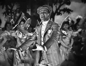 Cagney on stage and in costume, singing and dancing while the cast watches