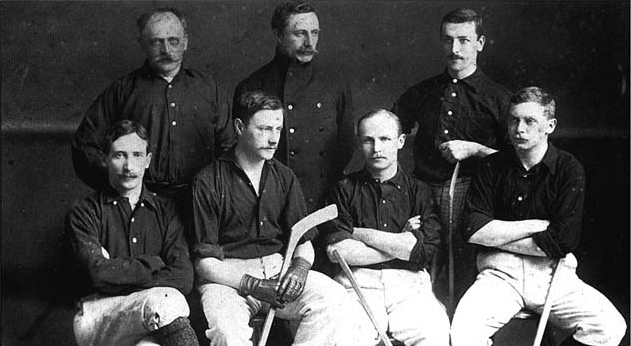 One row of four men seated with three men standing behind. Several have hockey sticks