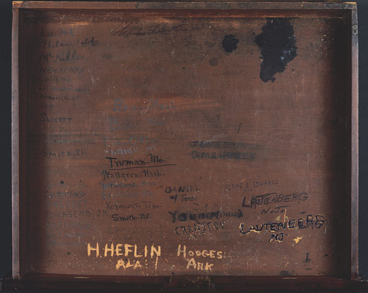 Inside of wooden desk with several names carved into it