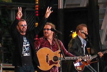 Starr is on stage with two guitarists and two microphones. He is wearing sunglasses and a black and silver T-shirt, and both of his arms are raised. His right arm forms a V-shaped peace symbol.