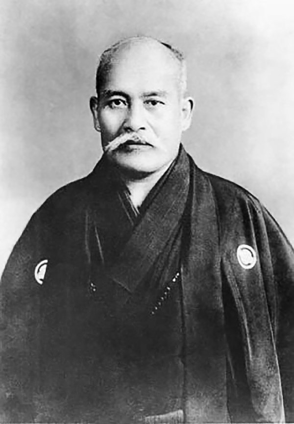 A middle-aged, mustachioed man in a kimono