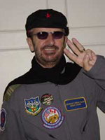 "A colour photo of Starr, who is holding two fingers up in the style of a ""peace sign"". He is a wearing a dark beret, sunglasses and a grey windbreaker with several patches on the front."
