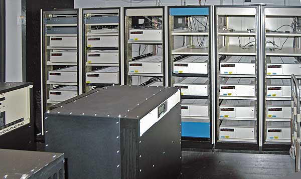 A room with a black box in the foreground and six control cabinets with space for five to six racks each. Most, but not all, of the cabinets are filled with white boxes.
