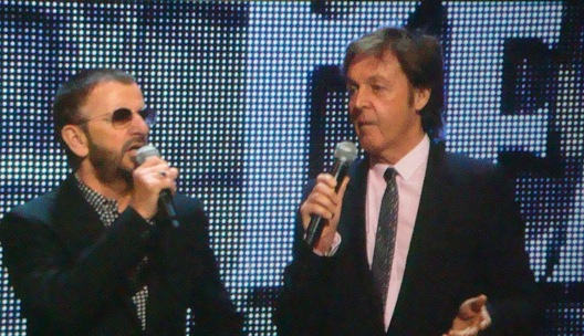 McCartney and Starr standing on a stage facing each other both with microphones held up to their mouths. Both men are wearing dark suits, McCartney is wearing a pink shirt, and Starr a black-and-white print.