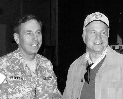 Middle-aged man in military uniform talking with older man in casual civilian clothes, at night