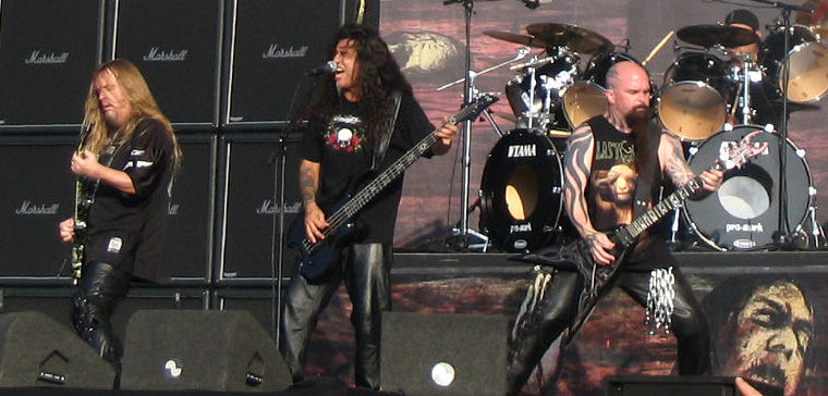 The band Slayer is shown at concert. From left to right are an electric guitarist, a bass player (also singing), an electric guitarists, and a drummer. The first guitarist and bassist have long hair. The right-most guitarist has a bald head. The drummer has two bass drums.