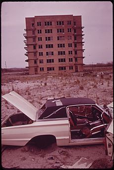 ABANDONED CAR AND UNFINISHED APARTMENT HOUSE CONSTRUCTION OF HIGHRISES ON BREEZY POINT PENINSULA WAS STOPPED BY CITY... - NARA - 547917