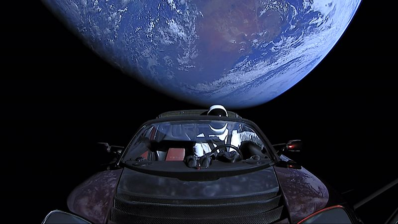 Large circular disc of a fully-illuminated planet Earth floating in the blackness of space. In front of Earth is a red convertible sports-car seen from the side. A humanoid figure wearing a white-and-black spacesuit is seated in the driving seat with the right-arm holding the steering wheel, and the left-arm resting on the top of the car door.