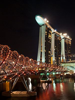 Spiral bridge spotted with red lights, spanning across a still river at night. A tall building with a boat-shaped top is in the background.
