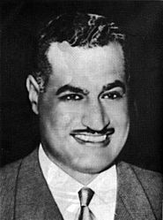 Head and shoulders of a man in his forties smiling. He has dark hair that is pulled back, a long forehead, thick eyebrows and a mustache.  He is wearing a gray jacket and a white shirt with a tie.