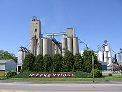 Sign welcoming visitors to Breckenridge, Michigan with large grain and corn silos rising above in the background