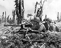 Three Marines and their machine gun lay heavy fire on a Japanese sniper nest (July 28, 1944).