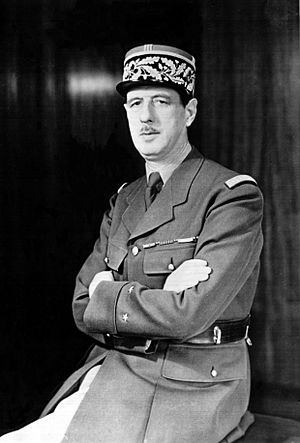 Charles de Gaulle seated in uniform looking left with folded arms