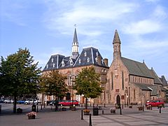 A square with three deciduous trees visible in the foreground. At the back of the square is the Town Hall, a neo-gothic style building. The town hall has two visible stories externally, together with a pitched roof with a number of dormers. In the centre of the roof area is a spire with a clock at its base. To the right of the Town hall is St Anne's church. The front of the church has a cylindrical cone spire.